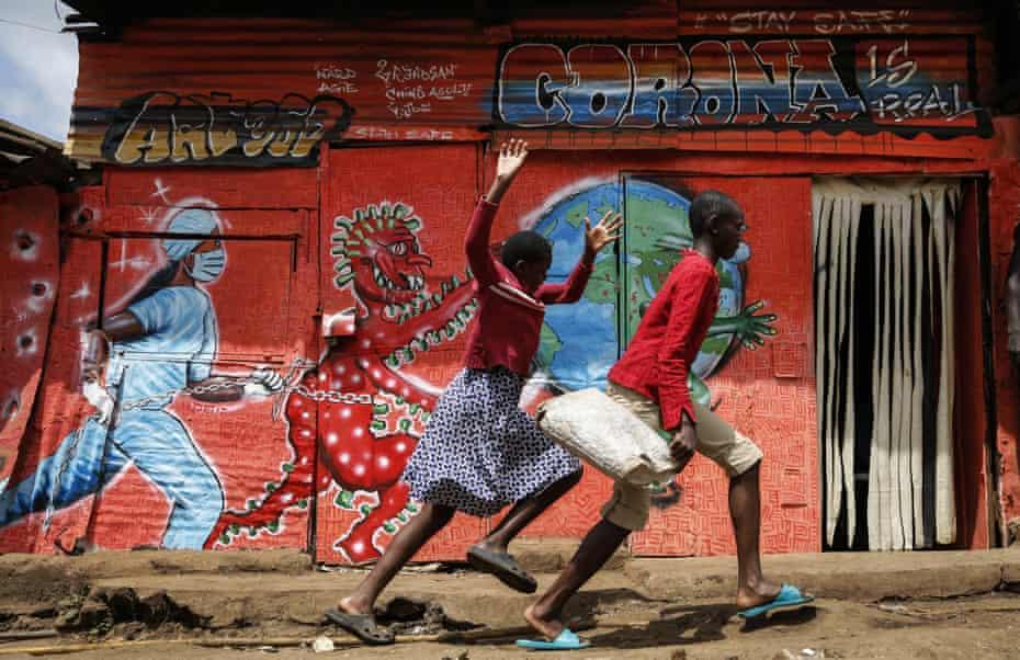 Children run past a mural featuring the coronavirus in the Kibera settlement in Nairobi, Kenya