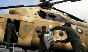 Pakistani soldiers load food bags on to a military helicopter