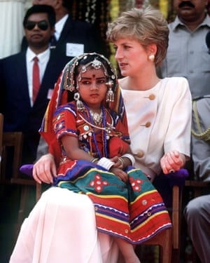 Hats off… A child in traditional costume sits on the Princess of Wales's lap at Lallapet high school in Hyderabad, India in 1992.