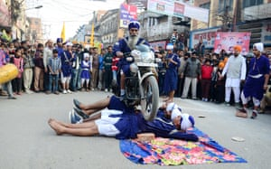 Allahabad, India: A Sikh rides a motorbike over men lying in the road