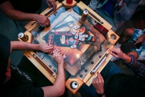 Puerto Ricans play dominoes, a popular game of luck and strategy commonly played in Puerto Rico, at La Placita, a restaurant by chef José Mendín that takes a modern approach to Puerto Rican food, in Miami, Florida.