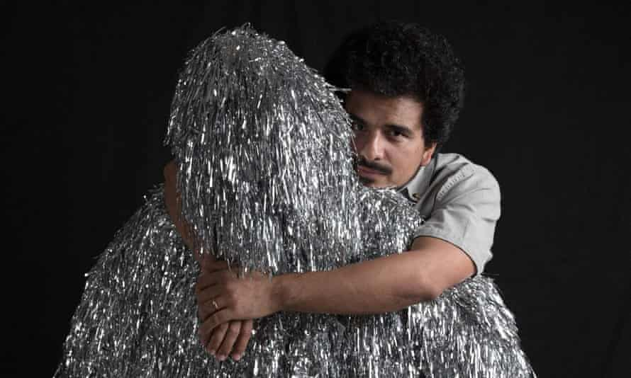 Helado Negro cuddling a Tinsel Mammal, one of the volunteers who dance with him on stage.