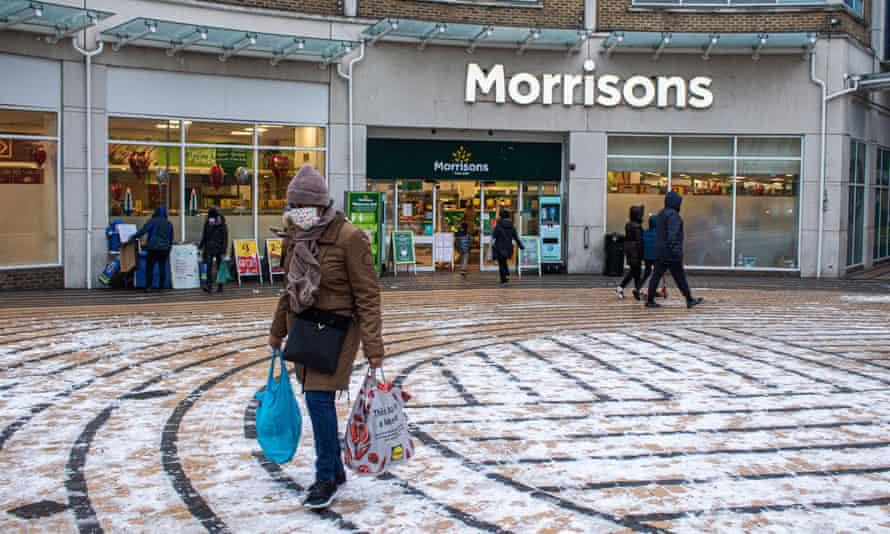 a woman passes a supermarket in the snow