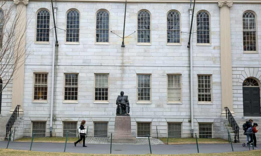 People walk past a statue of John Harvard on the university's campus in Cambridge, Massachusetts