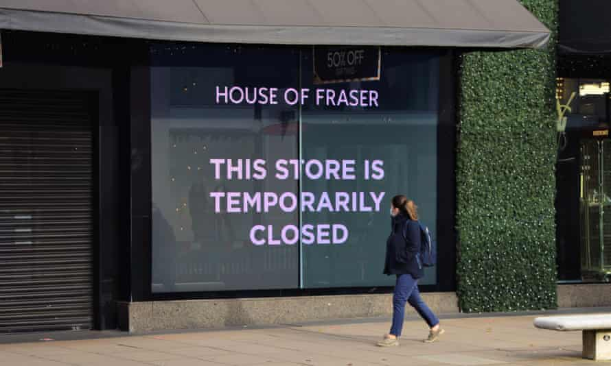 A woman with a face mask walking past a closed sign at House of Fraser department store
