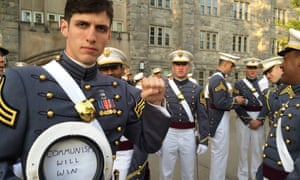 Spenser Rapone raises his left fist while displaying a sign inside his hat after graduating from the United States Military Academy at West Point.