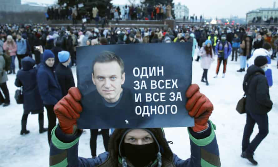 A man holds a poster of Alexei Navalny reading 'One for all and all for one', during a protest rally in St Petersburg.