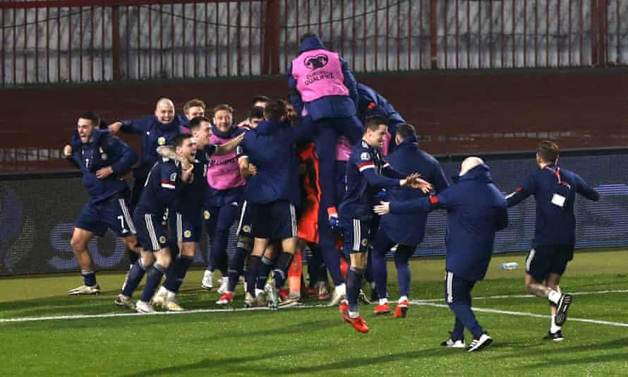 Scotland's players mob David Marshall after he saved Aleksandar Mitrovic's penalty to seal qualification for Euro 2020.