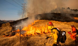 A back fire set by firefighters burns a hillside near PG&E power lines during firefighting operations to battle the Kincade fire in Healdsburg, California, in October.