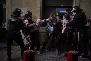 Riot police officers clash with protestors as they try to stop the eviction of Maite Mendibil, 58, from her apartment in Barcelona