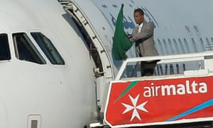 One of the hijackers waves a Gaddafi-era Libyan flag outside the plane