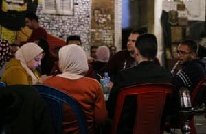 Egyptian youths smoke shisha outside a coffee shop in Cairo in February.