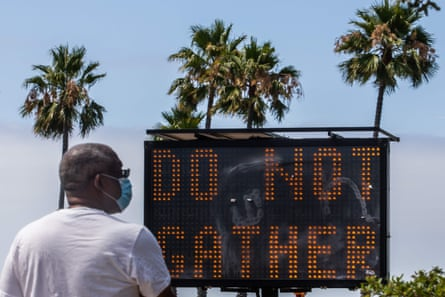 A man wearing a face masks checks his phone near a sign urging people not to gather in Long Beach, California, on 14 July.