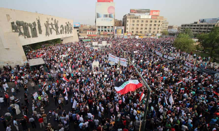 Iraqis wave their national flag during a demonstration against corruption and poor services in Baghdad.