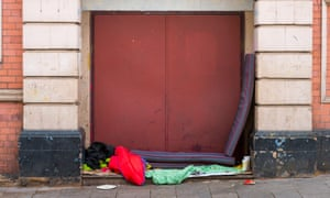 Sleeping bag and blankets left in a large doorway by a homeless person.