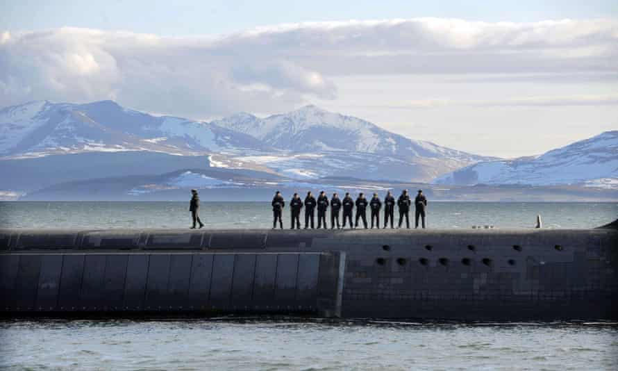Royal Navy personnel stand on top Trident nuclear submarine HMS Victorious off the west coast of Scotland.