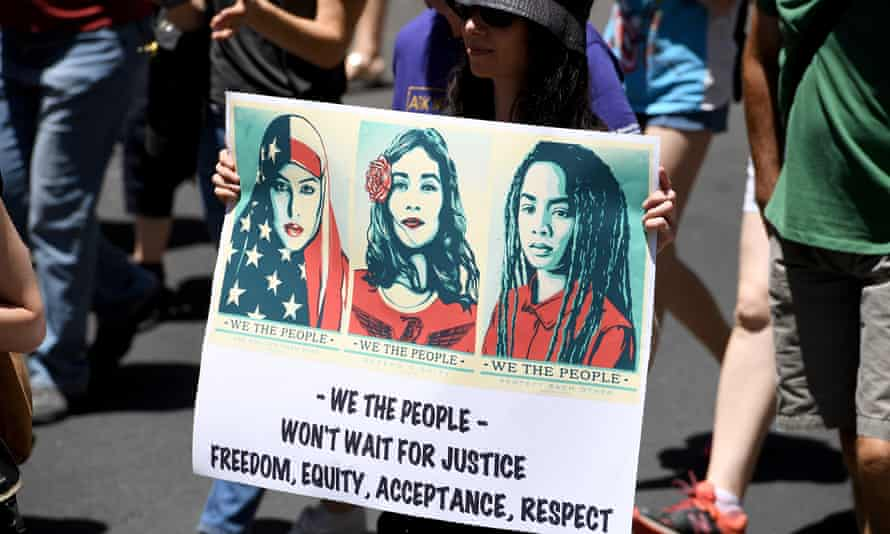 A protester in Sydney, Australia holds a placard with images from the We The People project designed by Shepard Fairey.