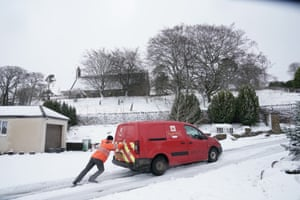 Nenthead, England A Royal Mail worker attempts to push a delivery van up a snowy road in Cumbria