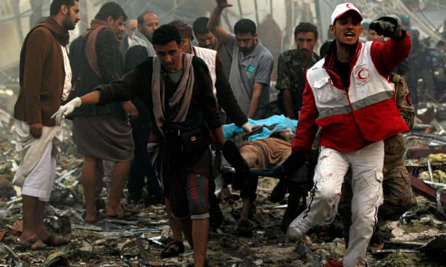 Yemeni rescue workers carry a victim on a stretcher amid the rubble of a destroyed funeral hall building following reported airstrikes by Saudi-led coalition air-planes on the capital Sanaa on October 8, 2016.