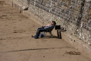 Sunbathers by the sea wall at Barry Island, Wales