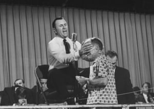 Faith healer Oral Roberts preaching, praying and laying hands on the sick.
