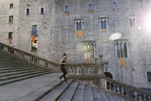 A woman jogs past a building decorated with Catalan flags in Girona