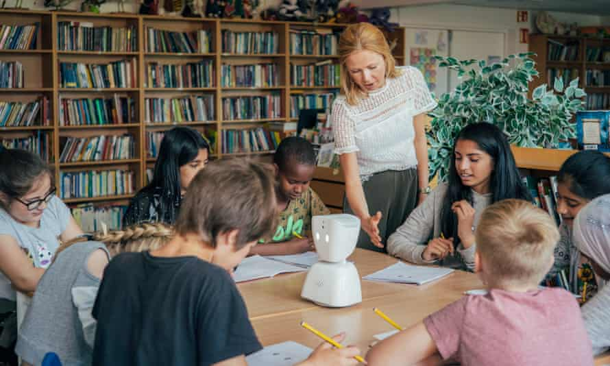 An AV1 robot on a classroom table surrounded by pupils and a teacher