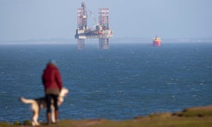 A clifftop dog walker passes the ENSCO-72 drilling rig in Poole Bay, Dorset