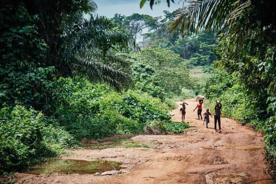 Cameroonian children walk along a dirt track