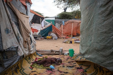 A young boy who has been displaced from his home by the drought sleeps outside the tent in the Mogadishu camp where he and his family live
