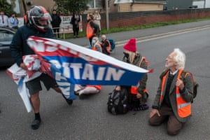 An angry motorist snatches a banner from Insulate Britain protesters blocking a junction near the Dartford Crossing