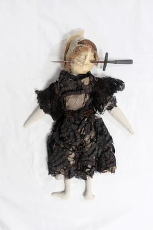 A 'poppet' of stuffed fabric in Edwardian-style black dress with stiletto through face, from 1909–13.