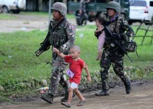 Filipino soldiers escort children in Marawi
