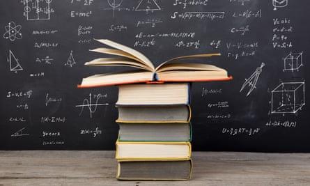 Books on the desk in the auditorium, formulas on the blackboard