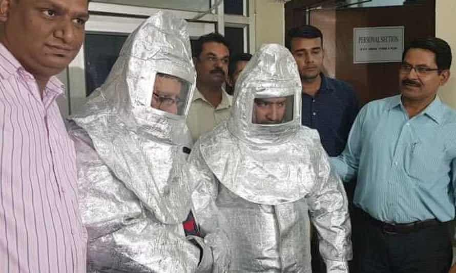 Indian officials stand alongside two men dressed in 'space suits' who were arrested for alleged fraud