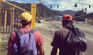 Two men walking along a street in Kingston, Jamaica, pictured from behind