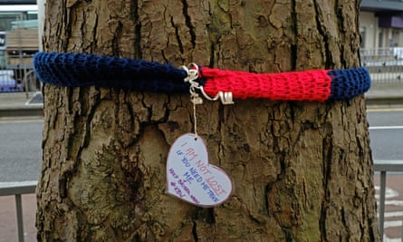 'I Am Not Lost' written on a heart pendant hanging from a blue and red scarf which is tied around a tree.