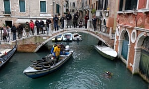 Scuba divers from Venice's gondolier association collect waste from the city's canals as part of a cleanup operation