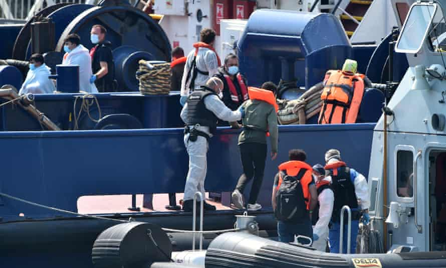UK Border Force officers help migrants to disembark from a coastal patrol vessel in Dover on 9 August.