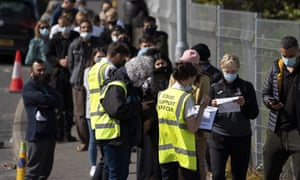 People queue for vaccinations against coronavirus at the ESSA academy in Bolton, England.