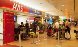 Holidaymakers queue at car rental desks at Malaga airport.