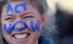 """A protestor with the writing 'Act now"""" on her face takes part in a protest march"""