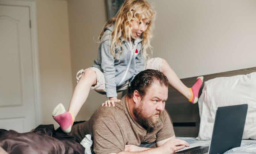Father working on laptop in bedroom with child daughter on his back