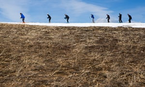 Skiers thread their way through patches of dry ground at California's Squaw Valley ski resort. Several Lake Tahoe-area ski resorts have closed due to low snowfall as California's historic drought continues.