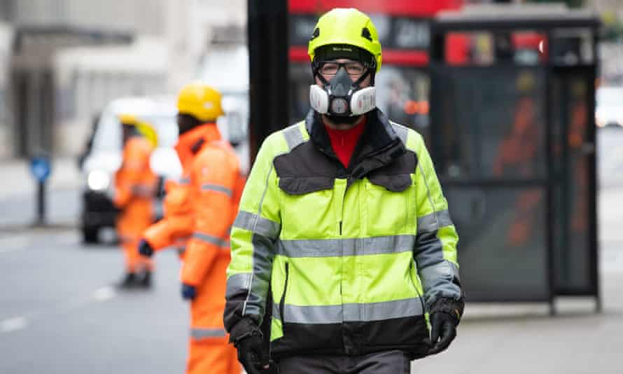 A construction worker wears a protective face mask in London before the lockdown.