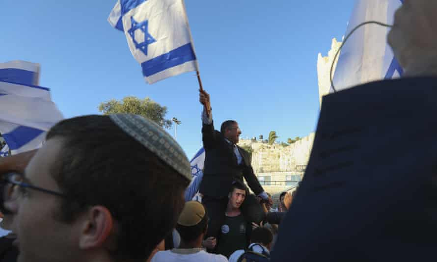 """Knesset member Itamar Ben-Gvir waves an Israeli flag together with other ultranationalists during the """"Flags March"""" in Jerusalem on Tuesday."""