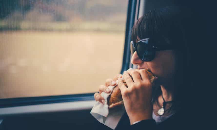 Woman on train eating a sandwich