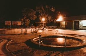 People enjoying a soak in the Artesian Bore Baths in Lightning Ridge, open 24 hours a day.