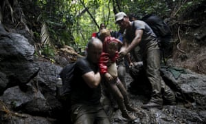 Cuban migrants help to carry a child as they climb down a slope crossing the border from Colombia through the jungle into La Miel, in the province of Guna Yala, Panama, last year.