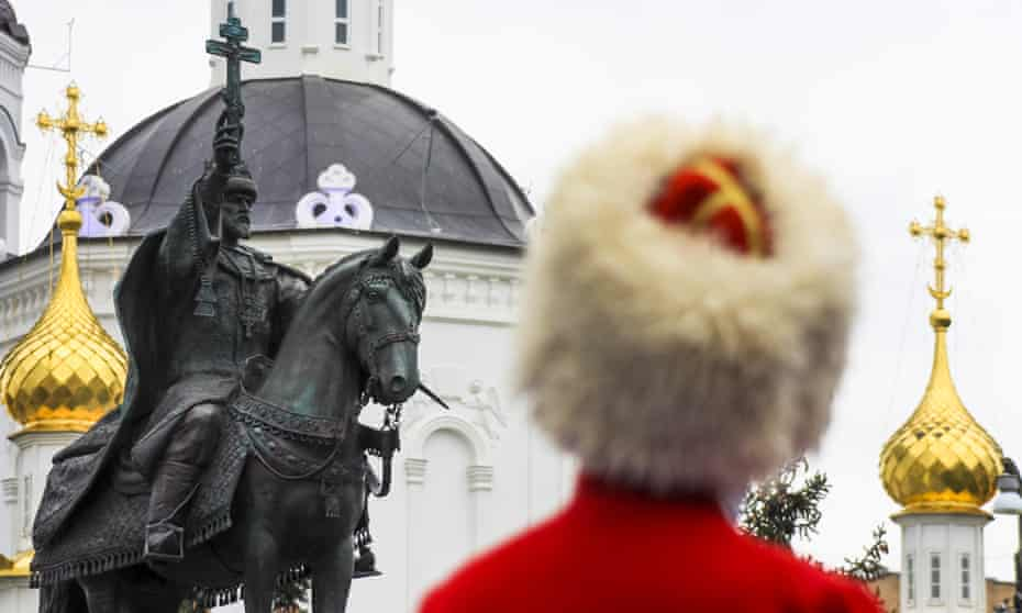 someone in a fur hat looks at the new statue, which is of a man on a horse waving a cross